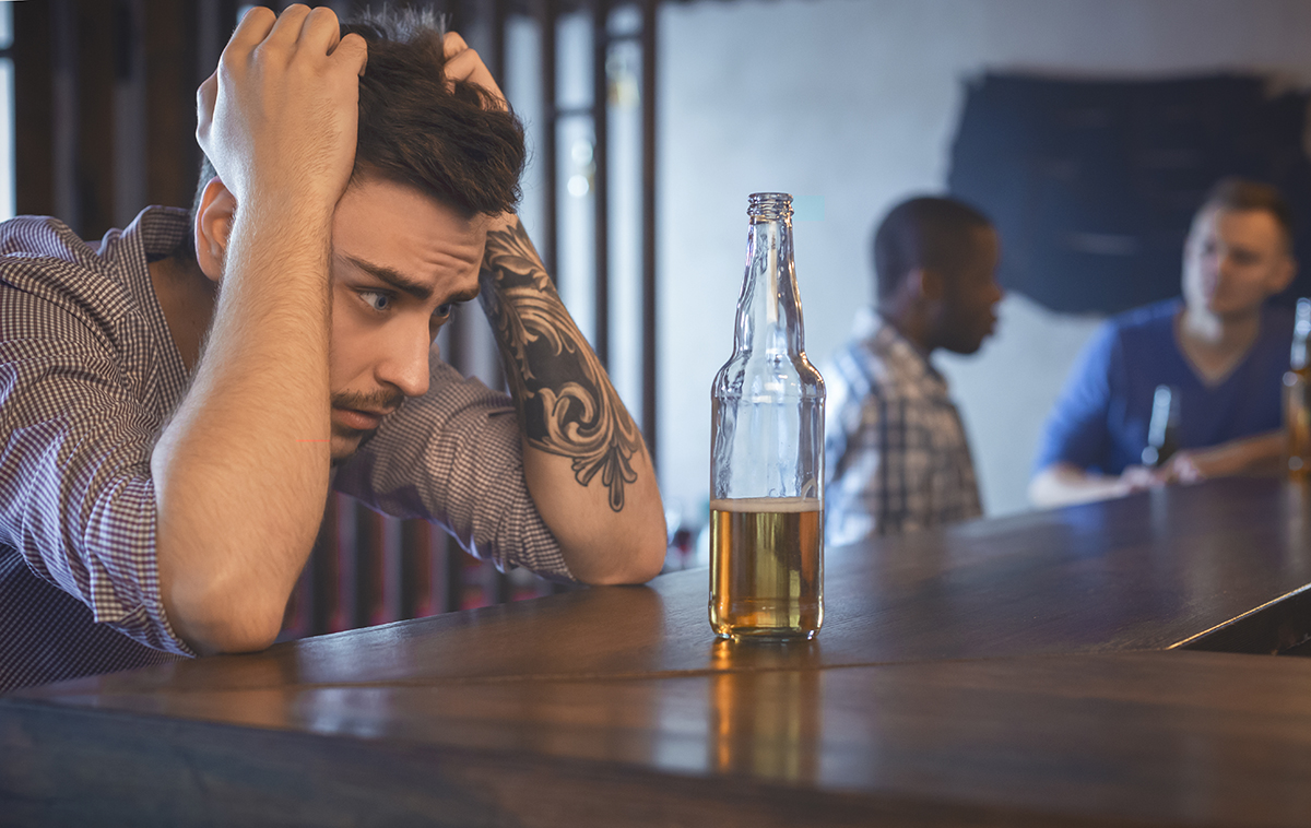 am i an alcoholic, young man staring at beer bottle in bar