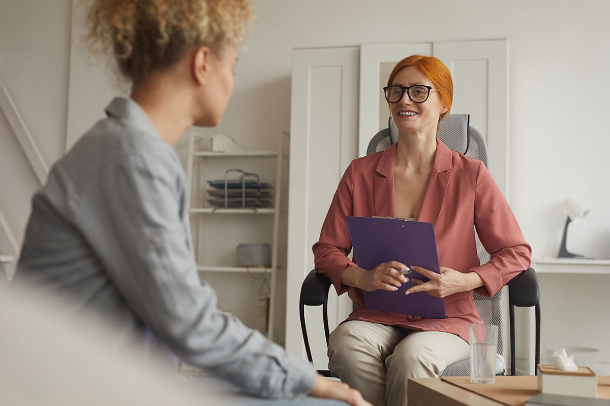 therapist smiling with patient explaining Importance of Dual Diagnosis Treatment