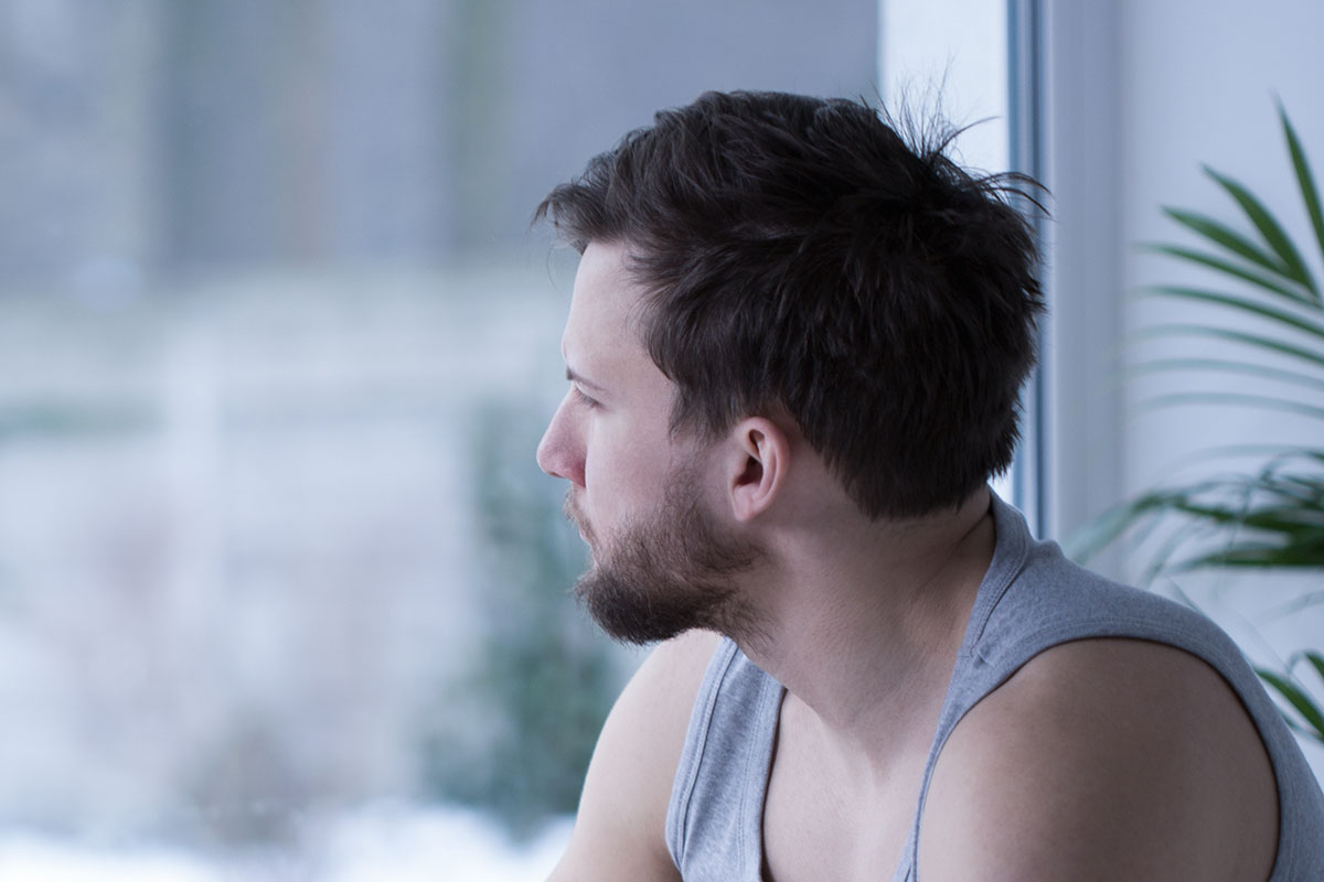 man staring out window showing signs of depression